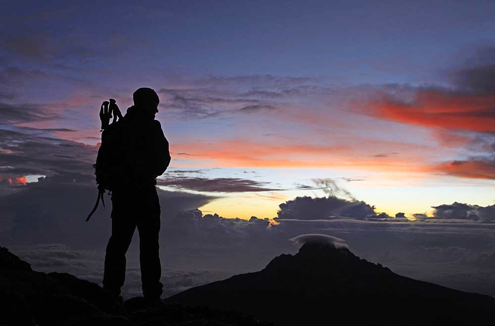 A climber looks towards Mawenzi from near the summit of Mount Kilimanjaro at dawn, Tanzania, East Africa, Africa