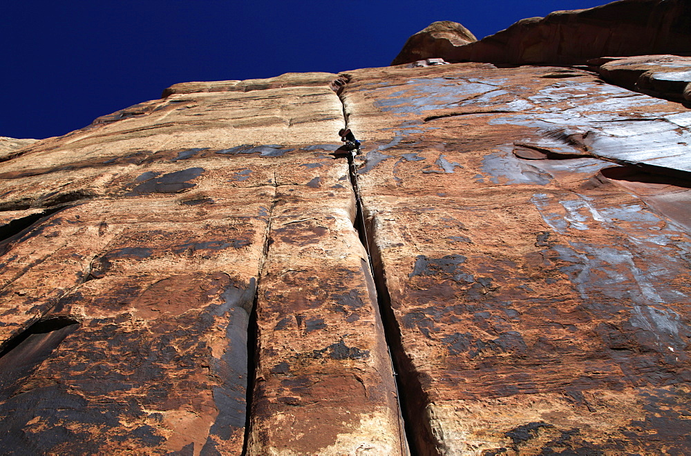 A rock climber tackles an overhanging crack in a sandstone wall on the cliffs of Indian Creek, a famous rock climbing area in Canyonlands National Park, near Moab, Utah, United States of America, North America