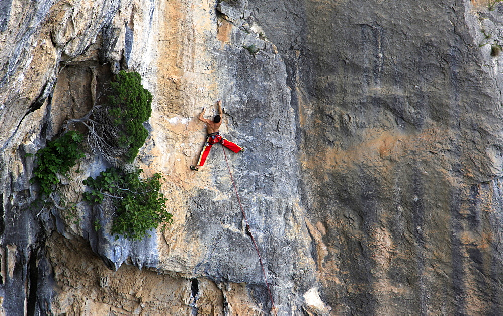 A man on a long and technically demanding face climb on the limestone cliffs of the Mascun Canyon, Rodellar, Sierra de Guara, Aragon, southern Pyrenees, Spain, Europe