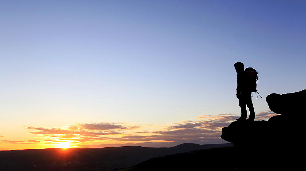 A hiker at sunset on Bamford Edge, near Edale, Peak District, Derbyshire, England, United Kingdom, Europe
