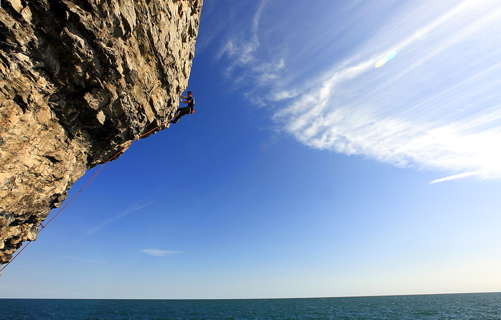 A climber scales cliffs near Swanage, Dorset, England, United Kingdom, Europe