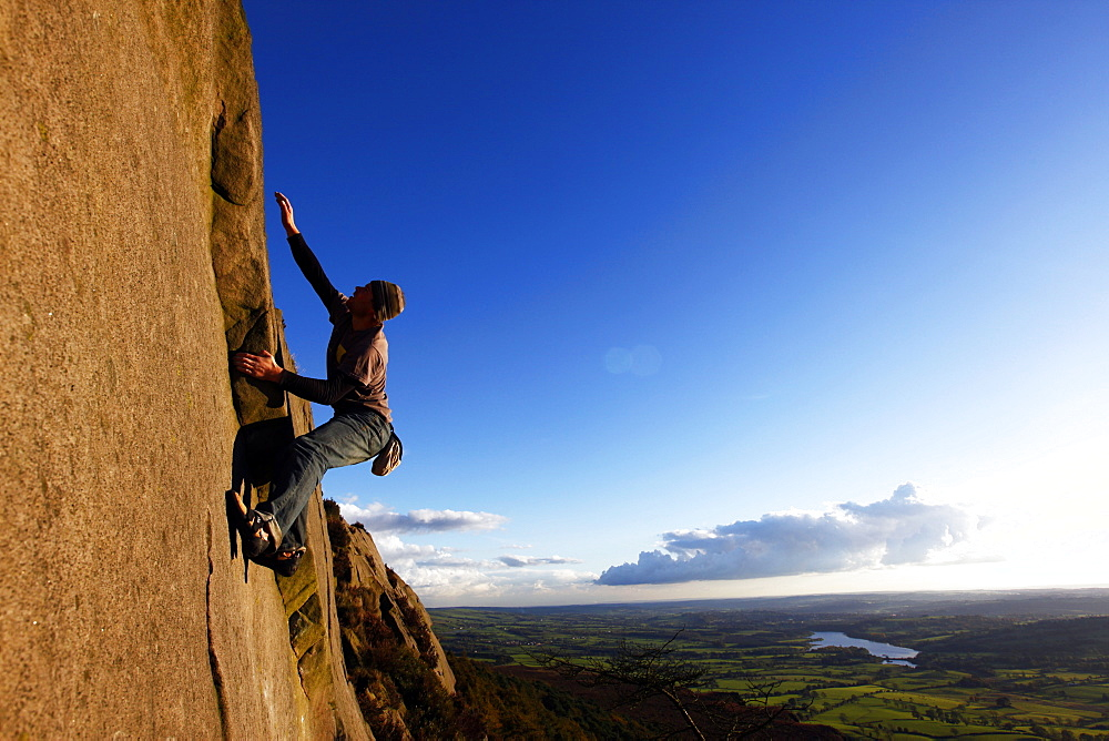 A climber scales cliffs at the Roaches, Staffordshire, England, United Kingdom, Europe