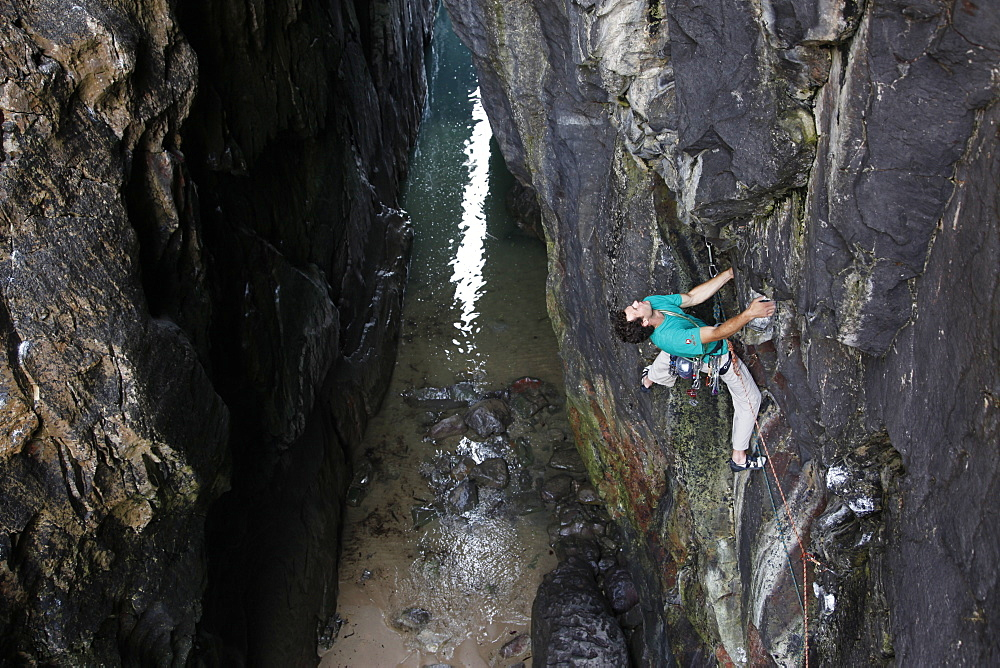 A climber scales cliffs at Huntsman's Leap, Pembrokeshire, Wales, United Kingdom, Europe
