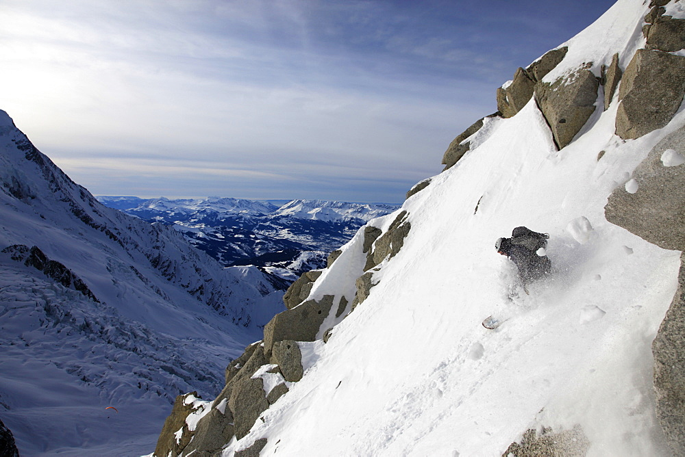 A snowboarder descending the famous Cosmiques Couloir, Chamonix Valley, Haute Savoie, France, Europe