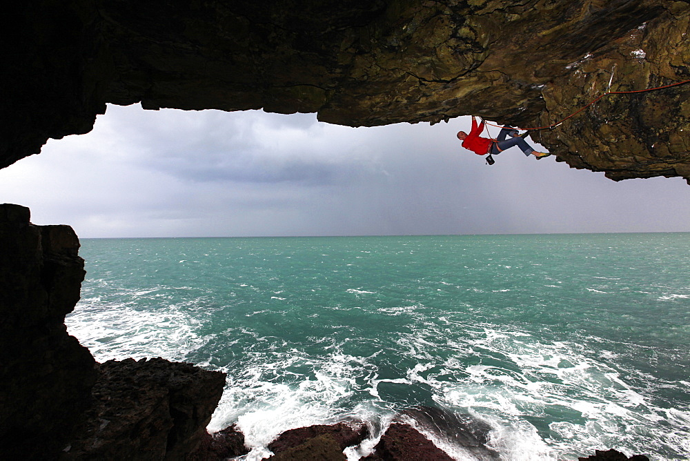 A climber scales a sea cave near Swanage, Dorset, England, United Kingdom, Europe