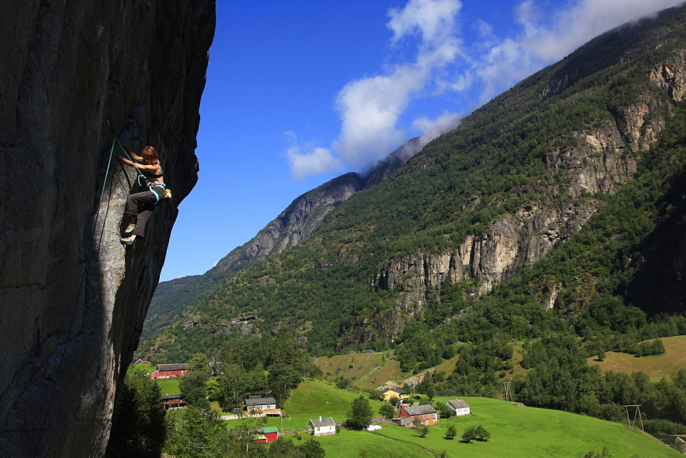 A female climber tackles a steep cliff at Loven, near Aurland, western Norway, Scandinavia, Europe