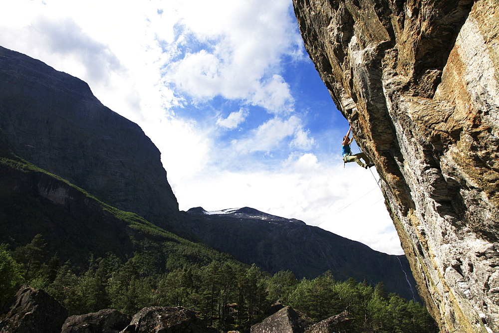 A woman climbs an overhanging route in Romsdal, near Alesund, western Norway, Scandinavia, Europe