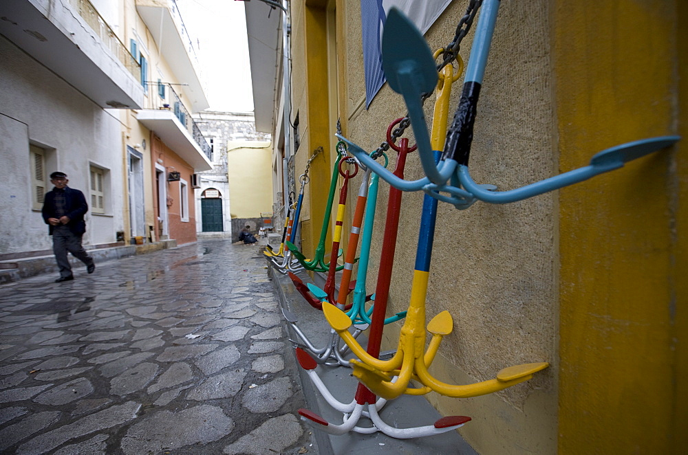 A local man walks past traditional Greek anchors for sale outside a chandler's store, Pothia Town, Kalymnos Island, Dodecanese, Greek Islands, Greece, Europe