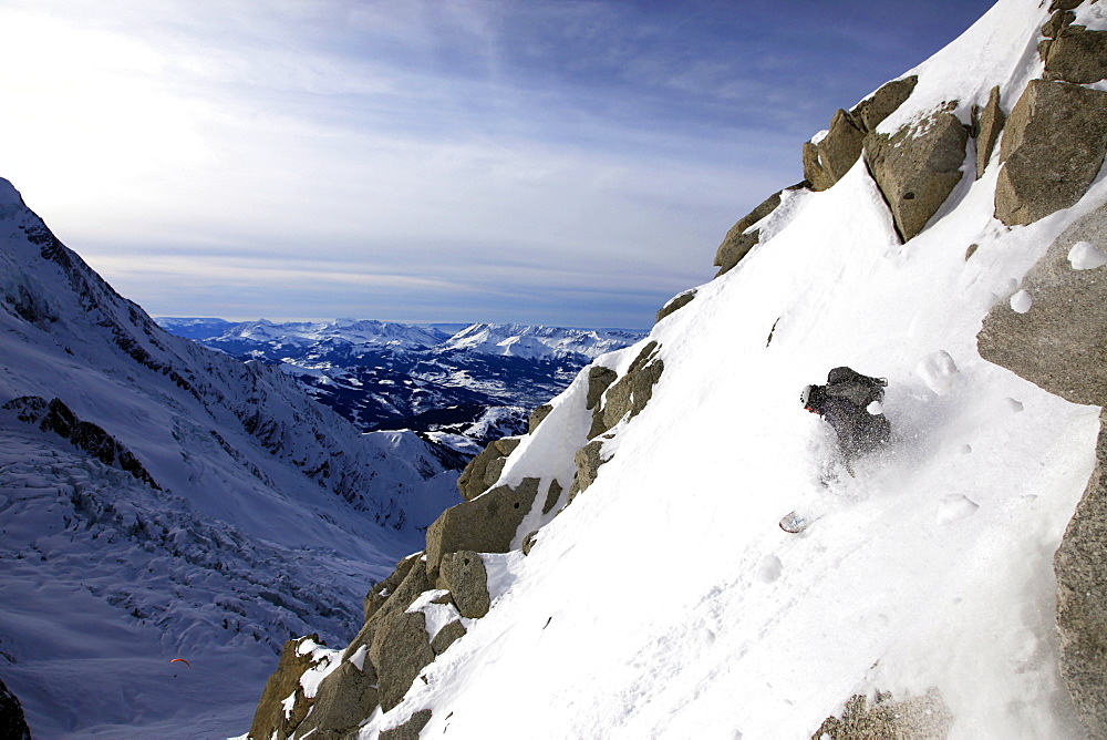 A snowboarder descends an extreme off piste route down Mont Blanc, Chamonix, Haute Savoie, France, Europe