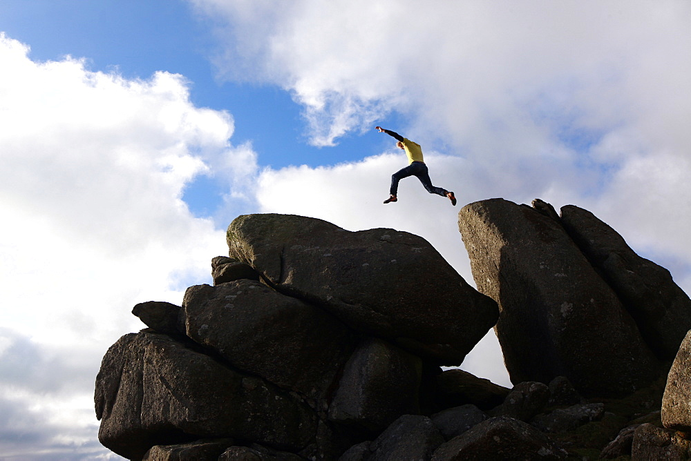 A parkour athlete jumping between boulders on Dartmoor, Devon, England, United Kingdom, Europe - 802-294