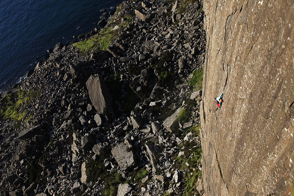 A climber scales the 100 metre cliffs at Fair Head, County Antrim, Ulster, Northern Ireland, United Kingdom, Europe - 802-299