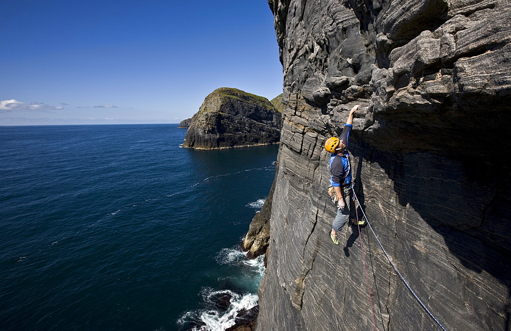 A climber hangs above the sea on the huge west face of Dun Mingulay cliff, Mingulay Island, Outer Hebrides, Scotland, United Kingdom, Europe