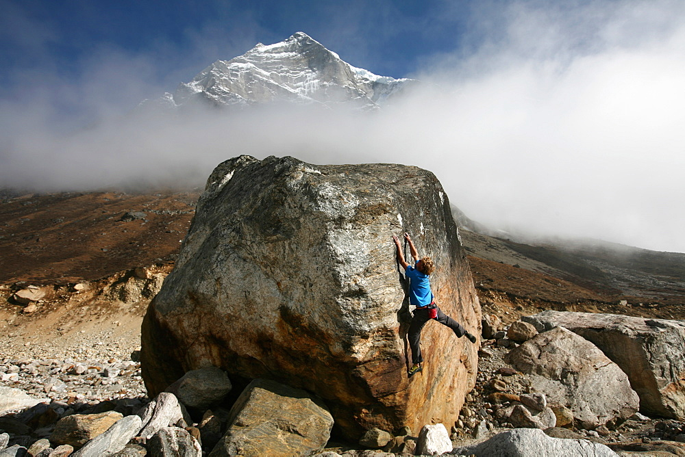 A climber tackles a difficult boulder problem on the glacial moraine at Tangnag, near Mera Peak and Mount Everest, Khumbu Region, Nepal, Himalayas, Asia
