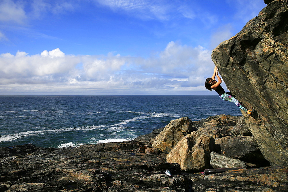 A climber bouldering by the sea near St. Ives, Cornwall, England, United Kingdom, Europe