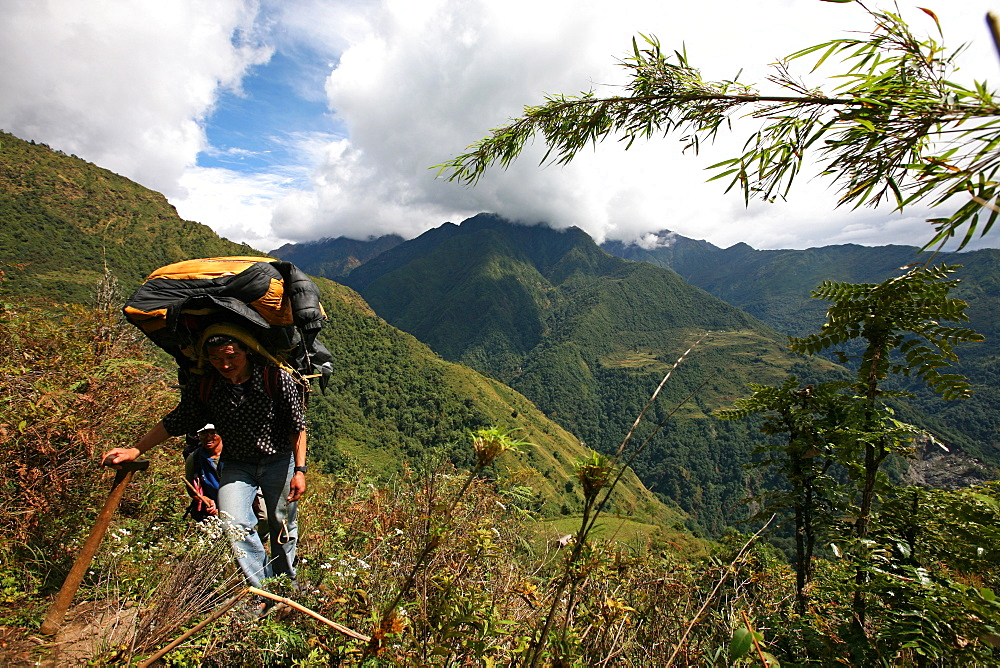 Nepali porter carries a heavy load using traditional wicker basket and tump headband in the lower Hingku Valley, close to Lukla and Mount Everest, Khumbu region, Himalayas, Nepal, Asia