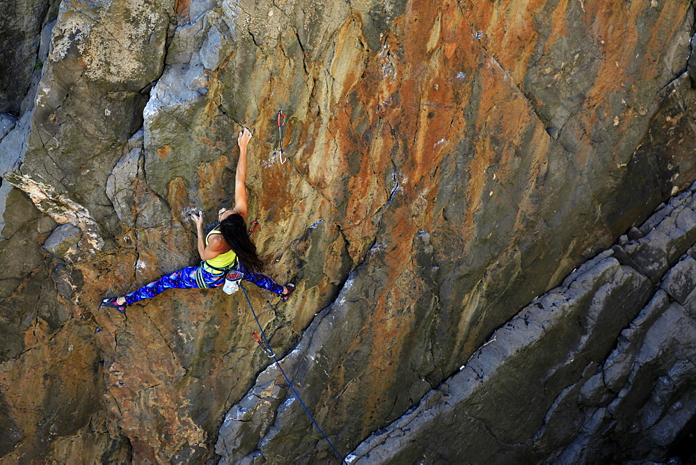 A woman rock climbing on cliffs on the Gower Peninsula, Wales