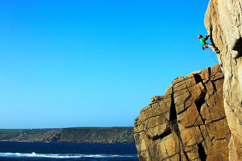 Rock climber in action on the cliffs of Sennen, Cornwall, England, United Kingdom, Europe