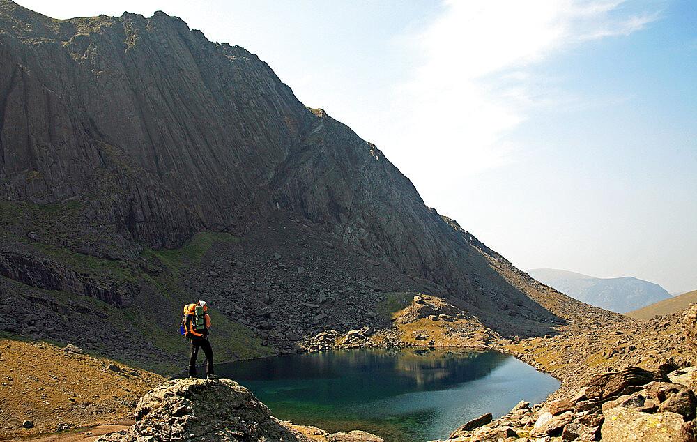 A hiker takes a break above Llyn Du'r Arddu, Snowdonia National Park, North Wales, United Kingdom, Europe