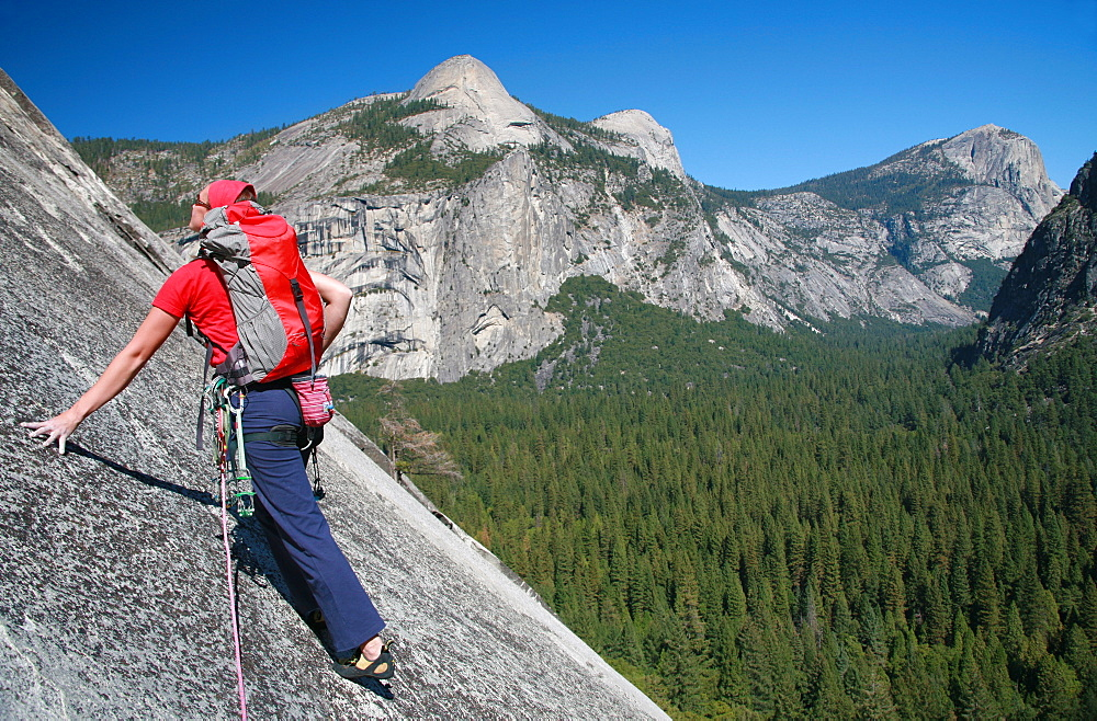 A rock climber ascends slabs at the base of the huge cliff known as The Apron, overlooking Washington Column and North Dome, Yosemite Valley, California, United States of America, North America