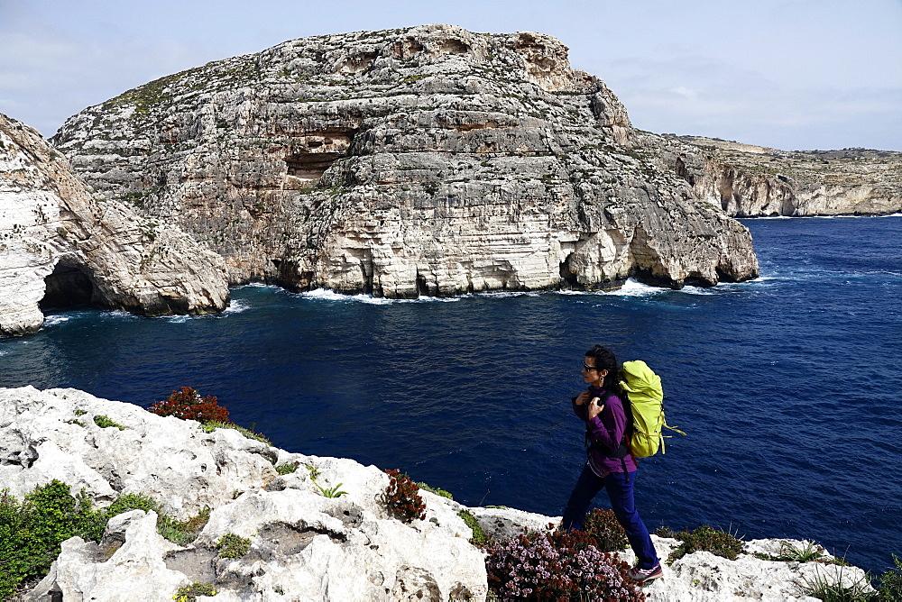 A woman hiking above sea cliffs near The Blue Grotto, south Malta, Mediterranean, Europe - 802-436