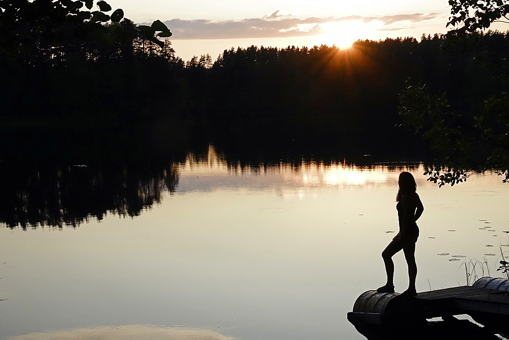 Woman looking out across a lake in rural Finland, Scandinavia, Europe