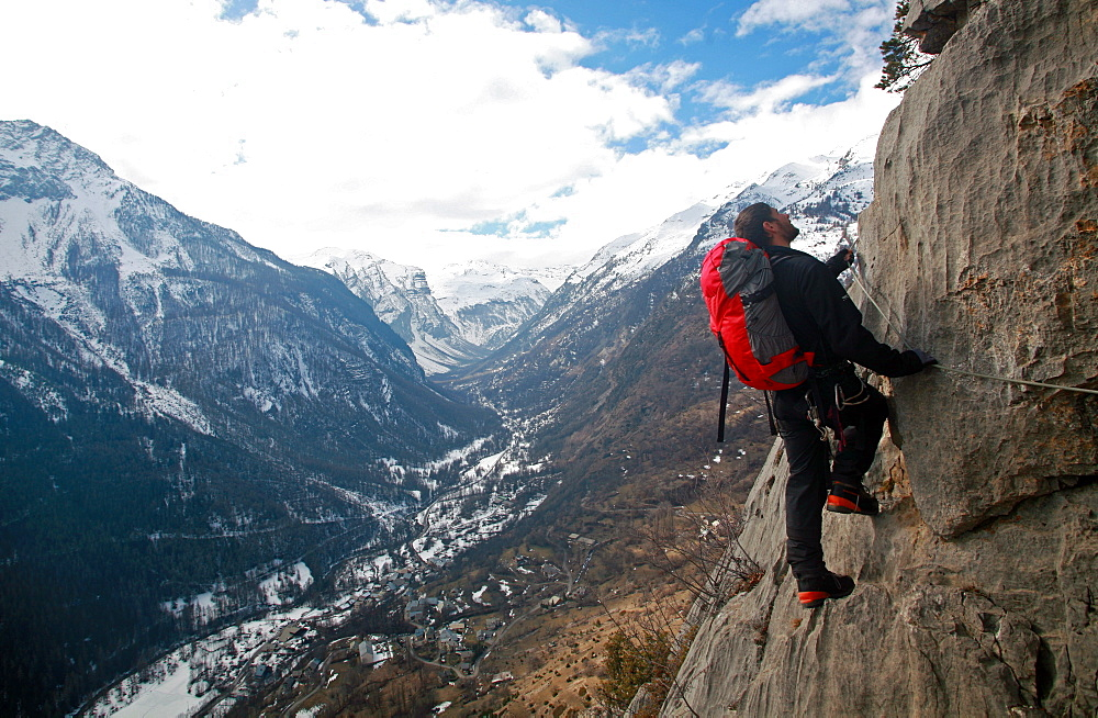 A climber moves along the steel cables on the Fressinieres via ferrata, above the Fressinieres valley, near Briancon, Ecrins Massif, western Alps, Hautes-Alpes, south east France, Europe