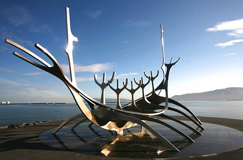 The midnight sun lights up the giant steel boat sculpture that stands on the water's edge at Reykjavik, Iceland, Polar Regions