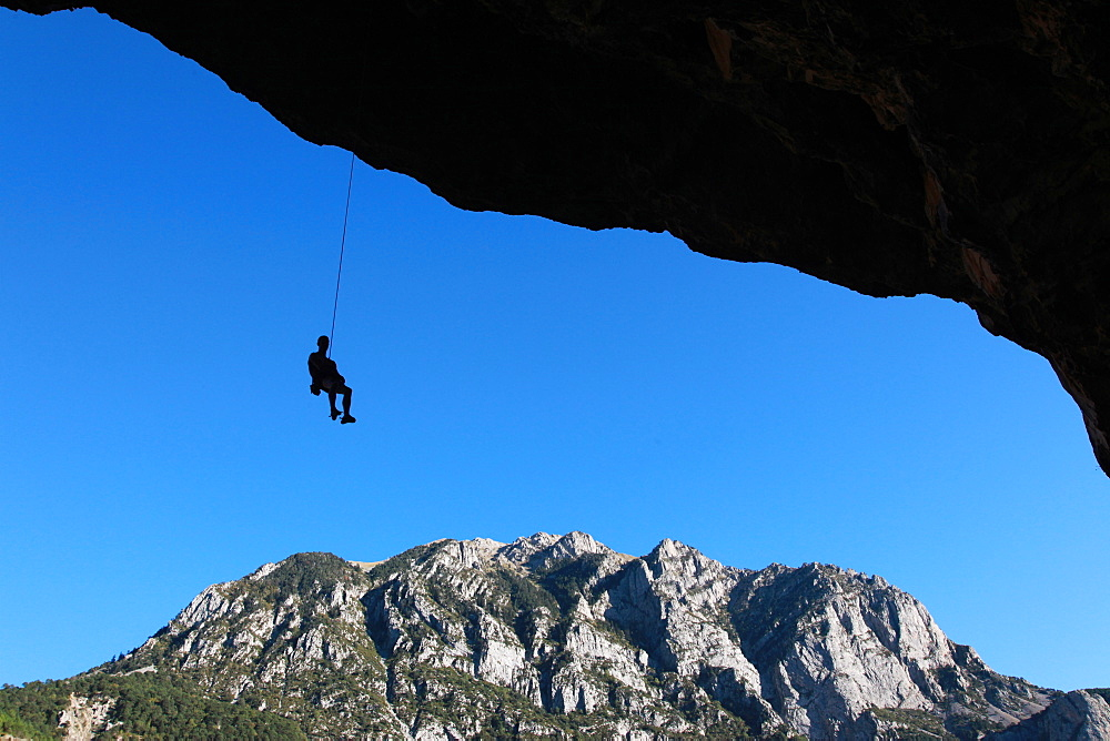 A climber lowers off a very overhanging cave climb on the cliffs above Bielsa, Spanish Pyrenees, Aragon, Spain