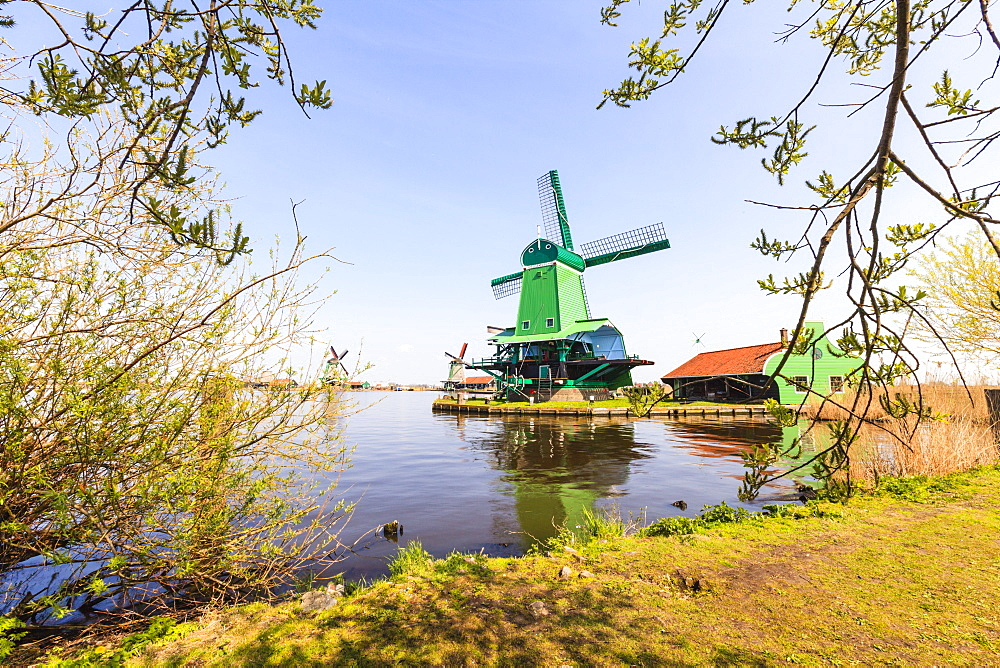 Preserved historic windmills and houses in Zaanse Schans, a village on the banks of the river Zaan, near Amsterdam, it is a popular tourist attraction and working museum, Zaandam, North Holland, Netherlands