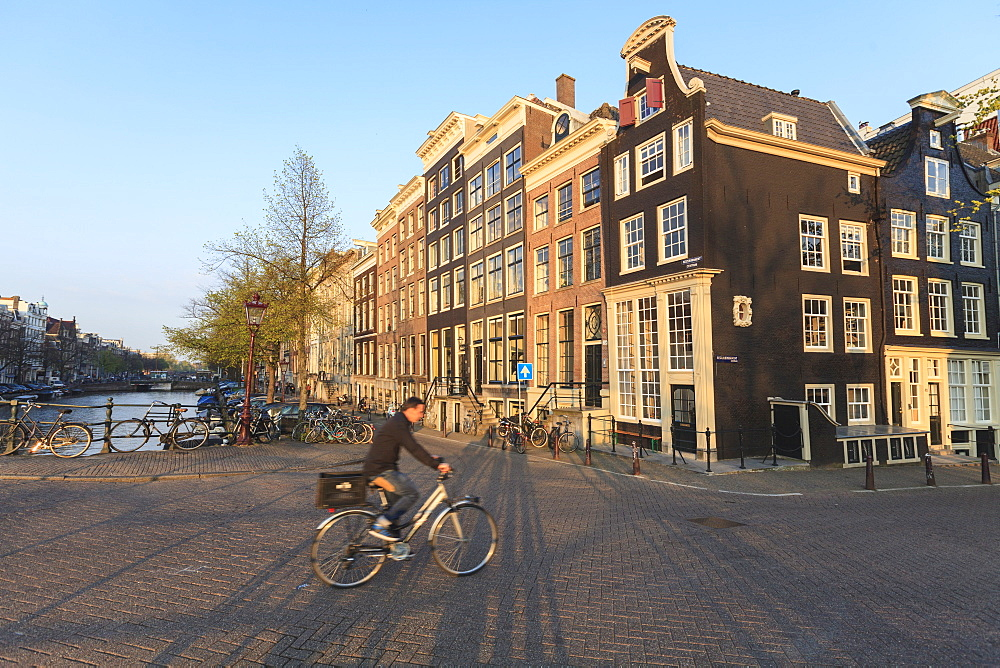 Cyclist crossing a bridge over Keizersgracht Canal, Amsterdam, Netherlands, Europe