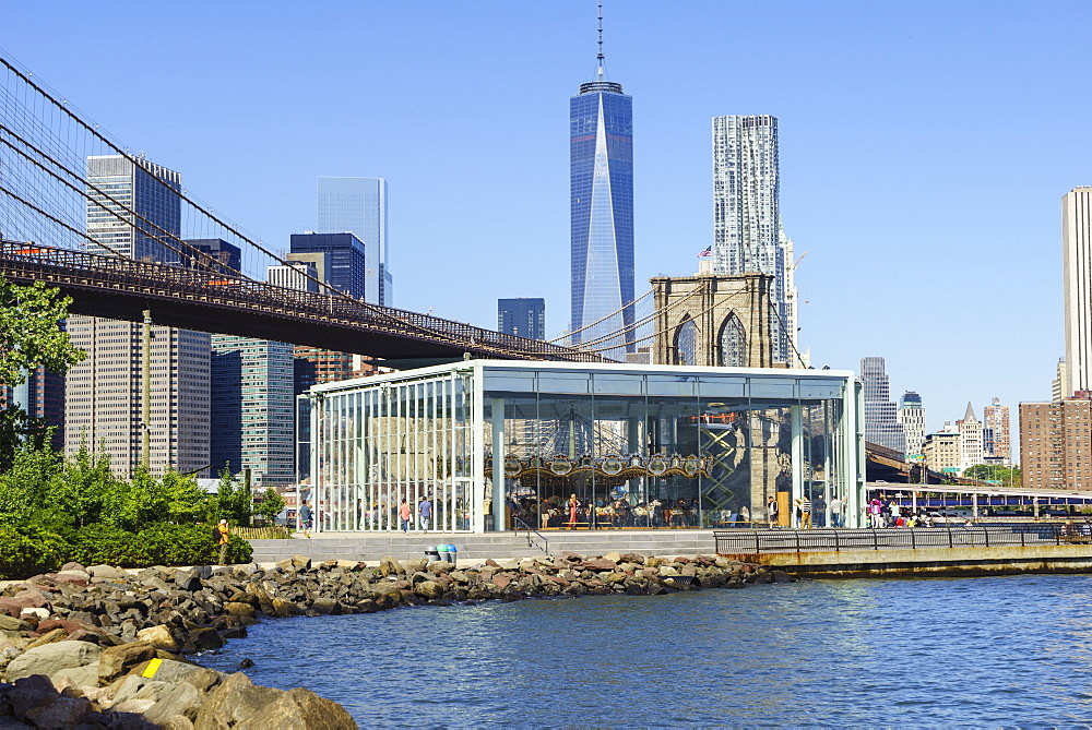 Jane's Carousel in Brooklyn Bridge Park with Brooklyn Bridge and Lower Manhattan skyscrapers including One World Trade Center beyond, New York City, New York, United States of America, North America