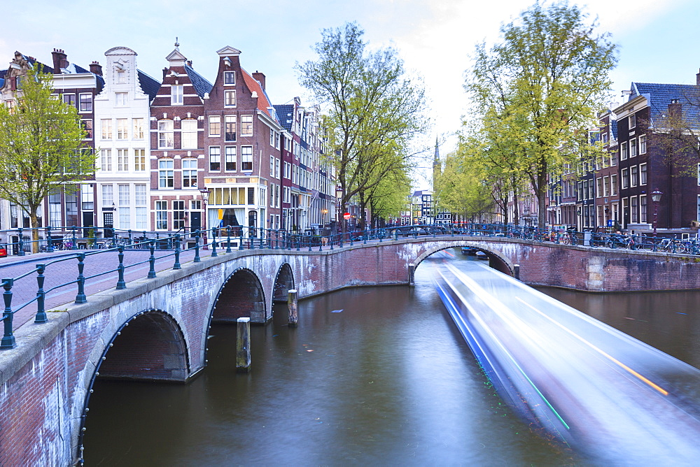 Long exposure of a tourist boat crossing canals Keizersgracht from Leidsegracht at dusk, Amsterdam, Netherlands, Europe