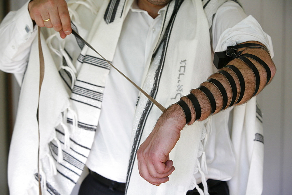 Rabbi putting on phylacteries, Paris, France, Europe