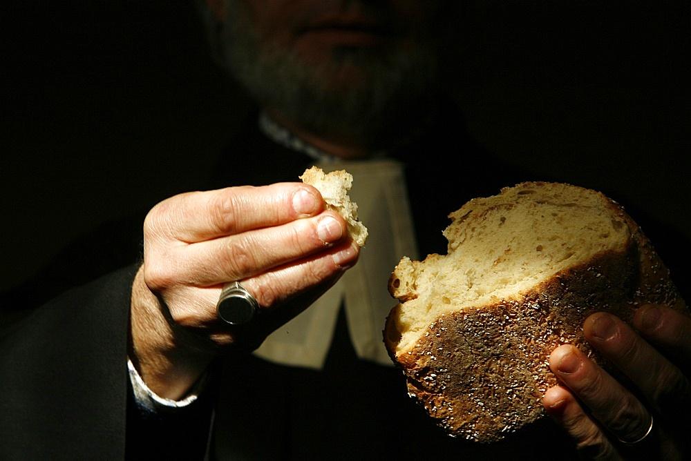 Protestant minister holding Communion bread, Geneva, Switzerland, Europe