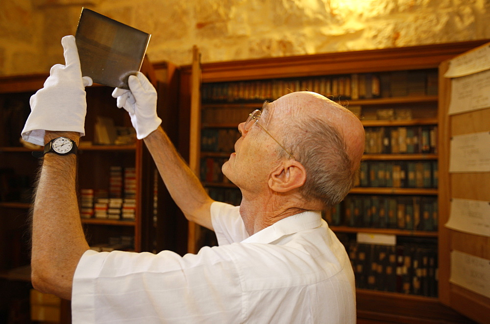 Father de Tarragon looking at photographic plates at the French Biblical and Archaeological School in Jerusalem, Israel, Middle East
