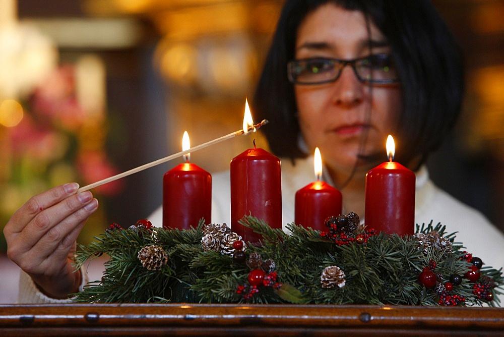 Woman lighting Advent candles, Saint-Nicolas de Veroce, Haute Savoie, France, Europe