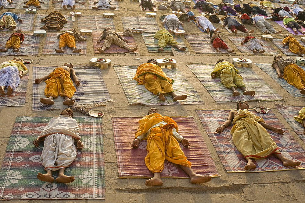 Students of a Sanskrit school performing the savasana (corpse) posture during daily yoga lesson at sunrise, on the ghat of Varanasi, Uttar Pradesh, India, Asia