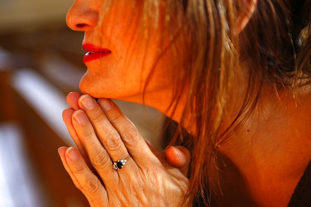 Woman praying in church, Haute Savoie, France, Europe