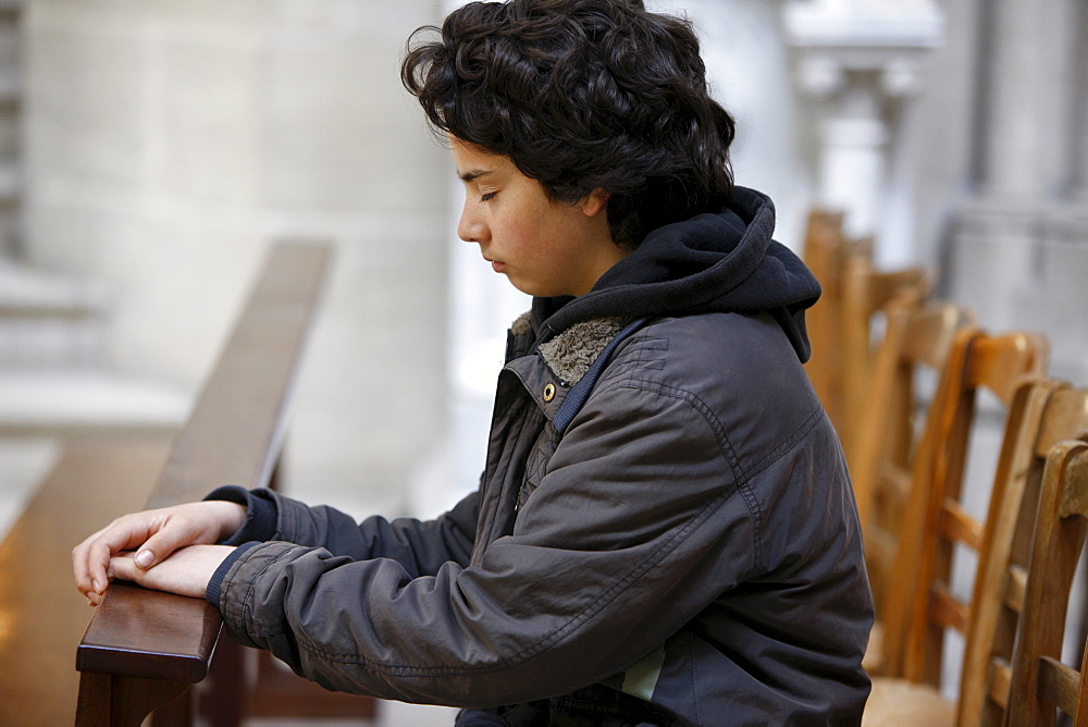 Teenager praying in Notre Dame de Bayeux cathedral, Bayeux, Normandy, France, Europe