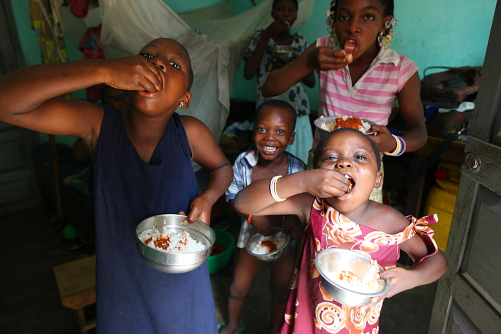 Children eating a meal, Lome, Togo, West Africa, Africa