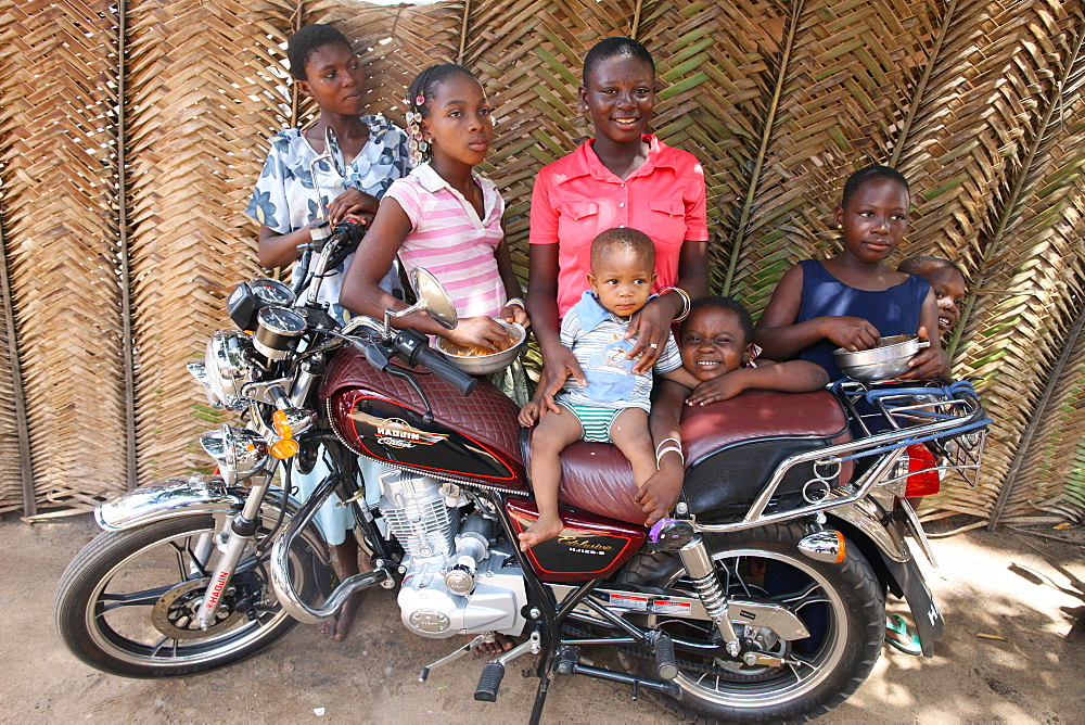 Family around a motocycle, Lome, Togo, West Africa, Africa