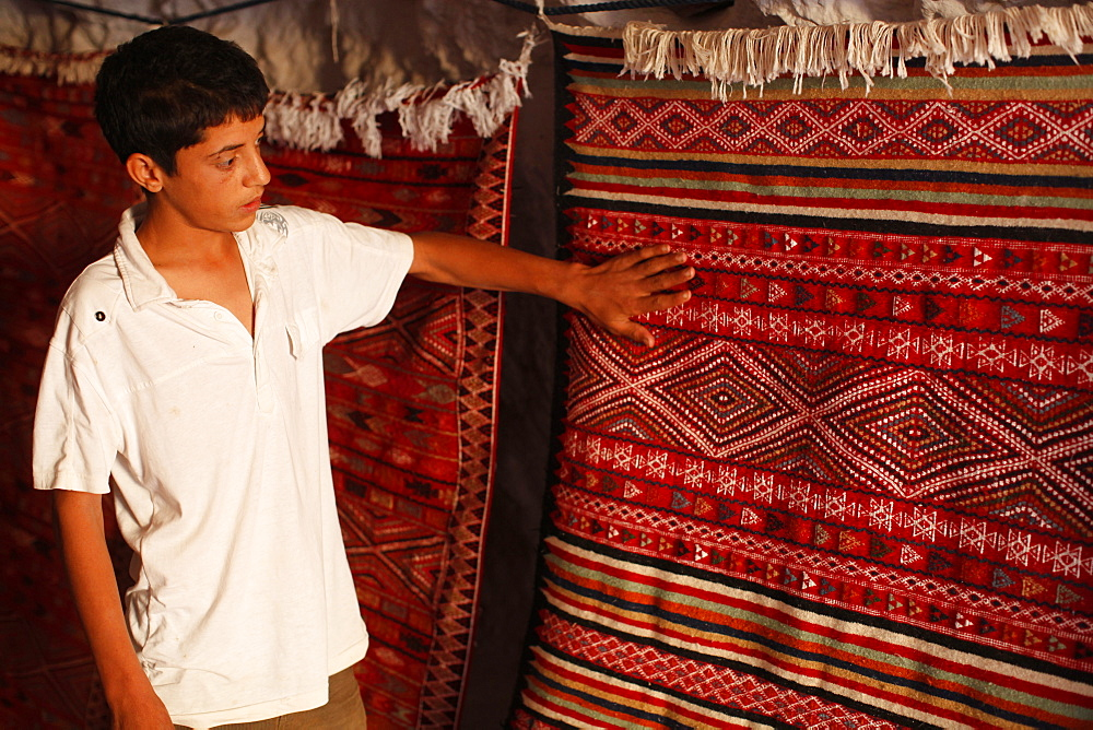 Boy showing a rug in a carpet shop, Toujane, Tunisia, North Africa, Africa
