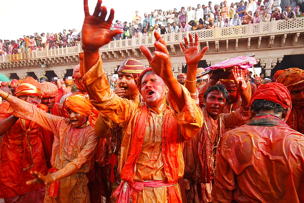 Barsana villagers celebrating Holi in Nandgaon, taunting Nandgaon villagers who throw colored fluids over them, Nandgaon, Uttar Pradesh, India, Asia