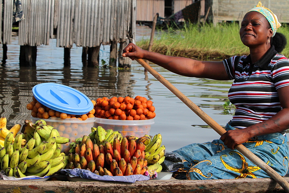 African woman mark paddling a canoe carrying fruit to market, Ganvie, Benin, West Africa, Africa