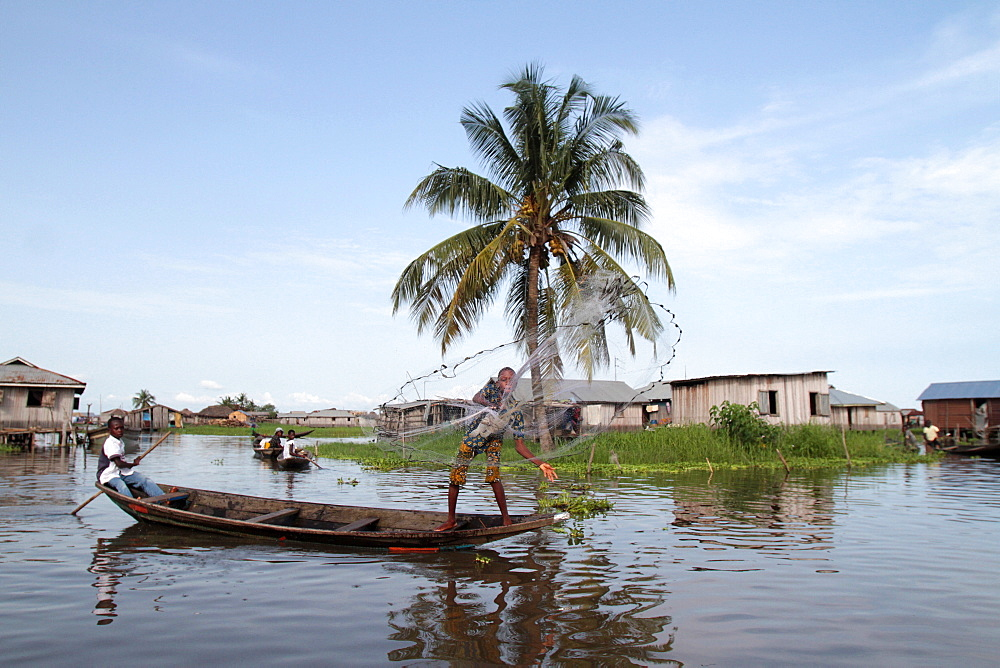 African children fishing with a net from a canoe, Lake Nokoue, Ganvie, Benin, West Africa, Africa