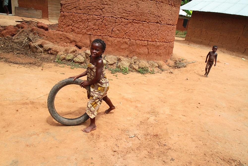 African girl having fun rolling an old tyre, Tori, Benin, West Africa, Africa