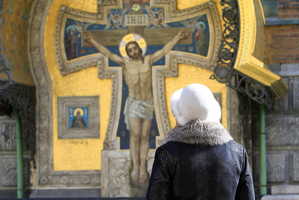 Russian woman praying in front of Christ, Church of Our Saviour on Spilled Blood (Church of Resurrection), St. Petersburg, Russia, Europe.