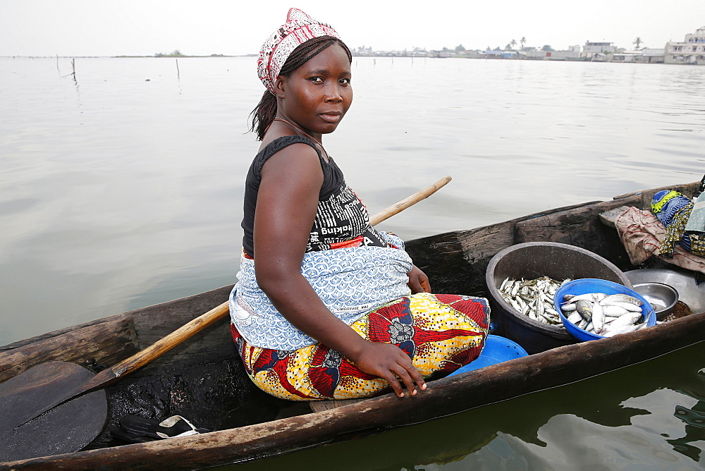 Fish seller on boat, Ayimlonfide-Ladji, Cotonou, Benin, West Africa, Africa