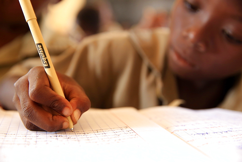 Pupil taking notes in French class in African primary school, Lome, Togo, West Africa, Africa