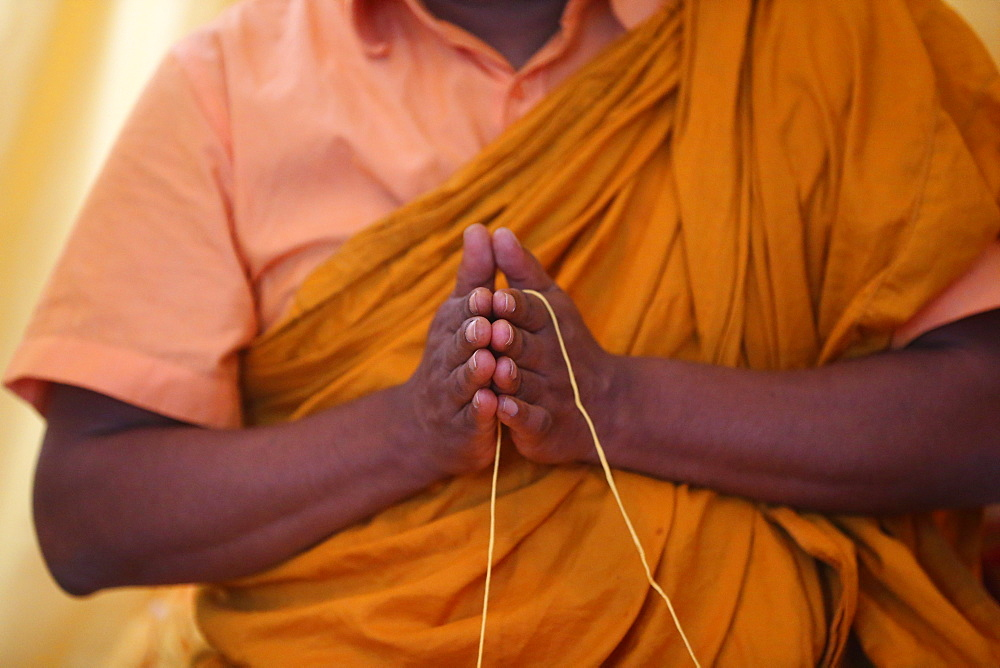 Monk praying, and Sai-Sin (sacred thread) in use in Buddhist ceremony, International Buddhist Center of Geneva, Geneva, Switzerland, Europe